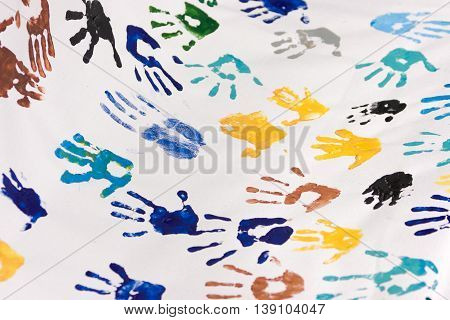 Background of colorful children hand prints. Many hand drawings on the white paper. Texture. Teamwork. Diversity.