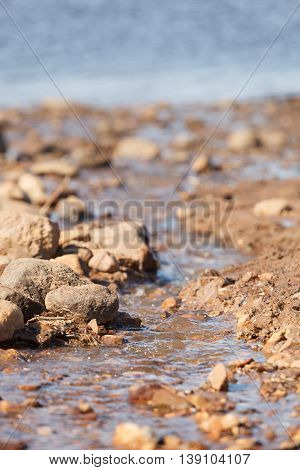Closeup of sand and stones on the sea shore. Sunlight at the beach. Water sand and stones on the coast of a ocean.
