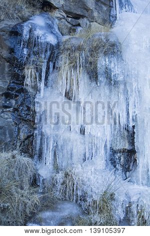 Frozen waterfall. Icicles. Ice river. Sani Pass - mountain pass between the borders of South Africa and Lesotho. Winter in Africa. Artistic retouching.