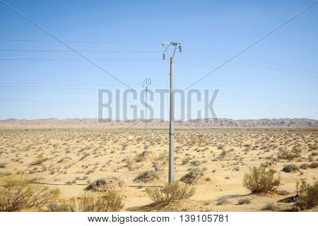 Power lines in rocky desert at the beginning of Sahara in the middle of Tunisia.