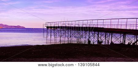 evening violet sky with silhouettes of wharf
