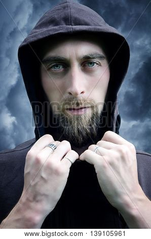Young bearded man in the hood on clouds background