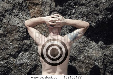 Man with target on his back on rock background
