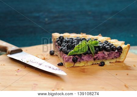 Last piece of blueberry pie decorated with basil leaves and knife on wooden board with copyspace