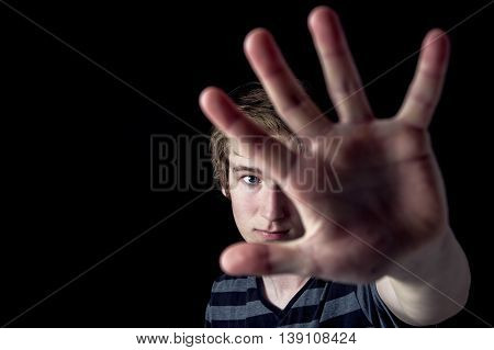 An image of a boy with his hand extended signaling to stop