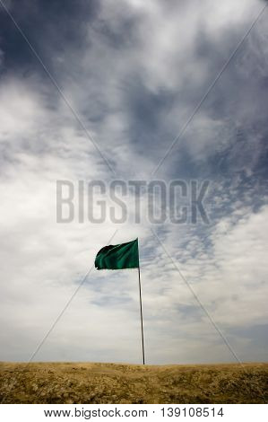 Green flag of victory in the remaining and untouched lands of Iran and Iraq war in Talaieh of Khozestan, Iran