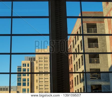 Shot taken from inside a city building looking outward at the surrounding buildings and parking garage.