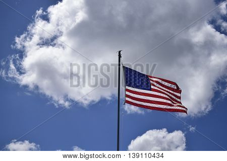 An American flag waving in the clouds.
