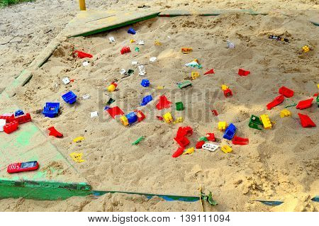 Children's playground with a sandbox and toys scattered