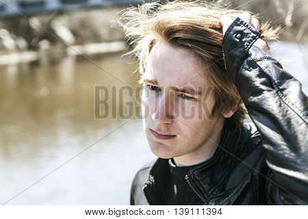 A teen sits outside close to a bridge Leather jacket.