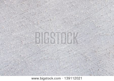 Abstract pattern of a white wall with small protruding stones, tiny holes and slight diagonal stripes