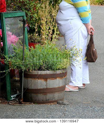 Overweight woman shopping a flea market outdoors.
