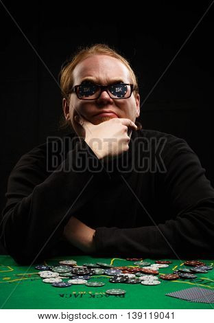 Beautiful young red-haired man in glasses and shirt with long sleeves sitting at poker table with cards and chips on it inserting two chips before his eyes at black background.