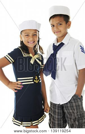 Two Hispanic siblings happily looking at the viewer as they stand together in their sailor outfits.  On a white background.