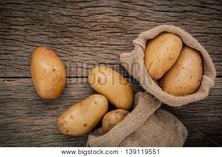 Fresh Organic Potatoes In Hemp Sake Bags On Rustic Wooden Background. Row Organic Potatoes  On Old W