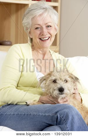 Senior Woman Holding Dog On Sofa