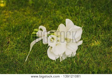 wedding bouquet of flowers calla on the grass