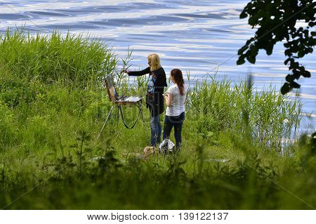 RUSSIA - JUNE 13 2016: Unidentified girl students draw a picture on an easel in the open air at the city lake June 13 2016 Russia