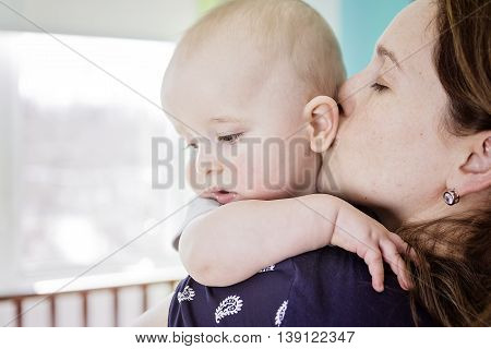 A Happy mother with her baby boy at home in bedroom