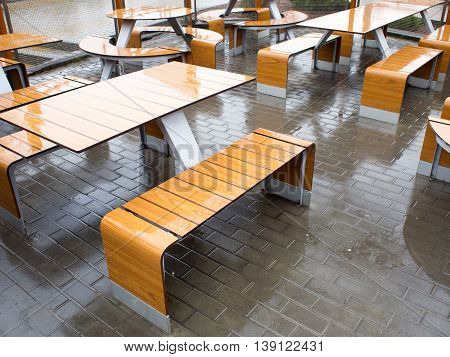 View of the outdoor cafe tables wet in the rain. Selective focus
