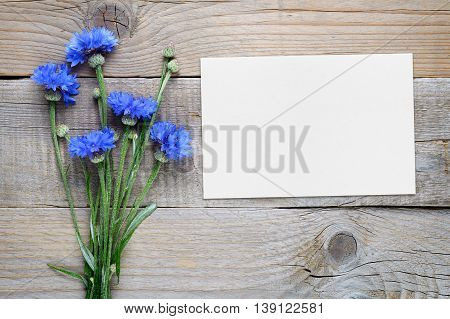 Cornflowers and blank card on wooden background