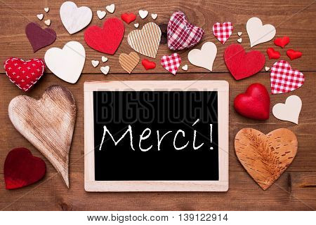 Chalkboard With French Text Merci Means Thank  You. Many Red Textile Hearts. Wooden Background With Vintage, Rustic Or Retro Style.