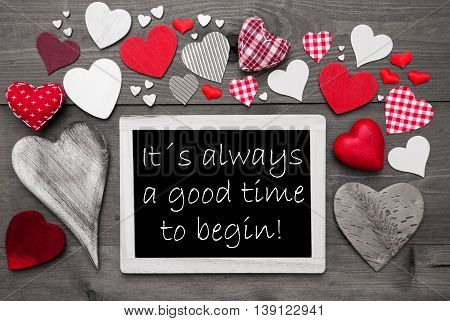Chalkboard With English Text It Is Always A Good Time To Begin. Many Red Textile Hearts. Grey Wooden Background With Vintage, Rustic Or Retro Style. Black And White Style With Colored Hot Spots