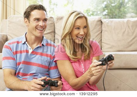 Young Couple Playing Computer Game On Sofa At Home