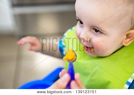 A Mother feeding hungry baby in the highchair indoors