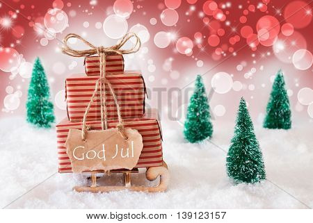 Sleigh Or Sled With Christmas Gifts Or Presents. Snowy Scenery With Snow And Trees. Red Sparkling Background With Bokeh Effect. Label With Swedish Text God Jul Means Merry Christmas