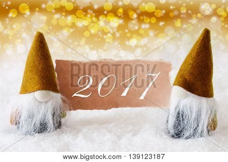 Christmas Greeting Card With Two Golden Gnomes. Sparkling Bokeh And Noble Background With Snow. Text 2017
