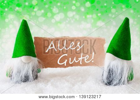 Christmas Greeting Card With Two Green Gnomes. Sparkling Bokeh And Natural Background With Snow. German Text Alles Gute Means Best Wishes
