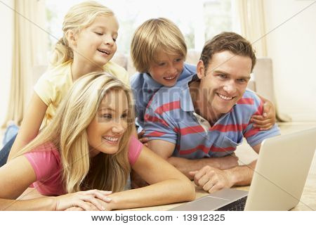 Family Using Laptop At Home Together