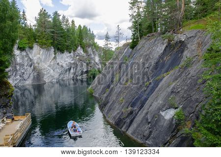 Marble canyon in Karelia, the natural Park of Ruskeala in Russia. Marble the pit for the extraction of marble in the past. Tourist place to travel. Stone cliff landscape of mountains and sky.