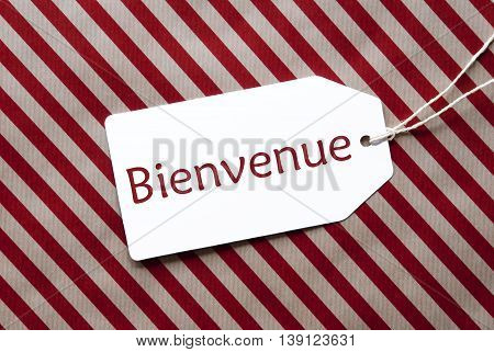 One Label On A Red And Brown Striped Wrapping Paper. Textured Background. Tag With Ribbon. French Text Bienvenue Means Welcome