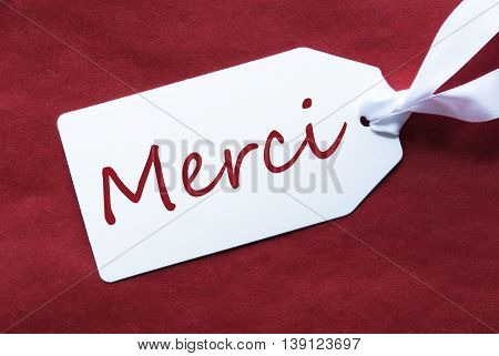 One White Label On A Red Textured Background. Tag With Ribbon. French Text Merci Means Thank You