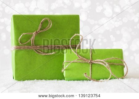 Two Green Christmas Gift Or Present On Snow. Card For Birthday Or Seasons Greetings. Natural looking Ribbon. Background With White Bokeh Effect