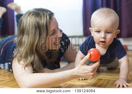 A Happy mother and her 1 year old son playing with small ball at home.