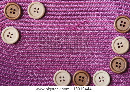 Wooden craft buttons on a pink background.