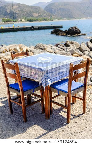 Wooden table with chairs near sea coastline