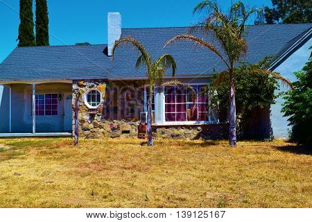 Foreclosed home with a dried up lawn and Palm Trees