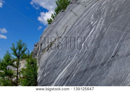 Rock with cut raw surface of white and grey mineral marble in natural environment of the North. Marble career and the place. Background stone, industrial material for making buildings and interior.
