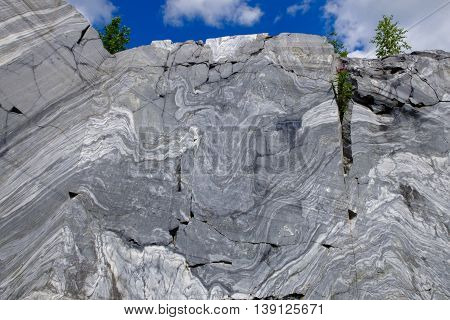 Rock cut raw surface of white and grey marble in the natural environment of the North. Marble career and the place. Background stone, industrial material for making buildings and interior.