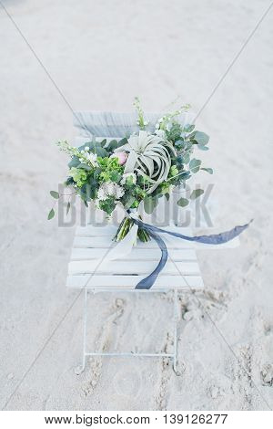 Wedding bouquet on a chair at the seashore.