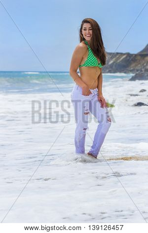 A brunette model posing on a beach