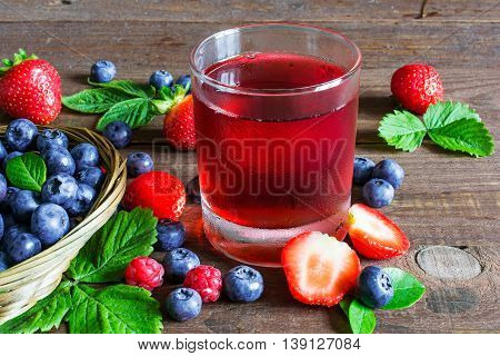 glass of cold summer berries juice with ripe berries in a wicker bowl and around on rustic wooden background