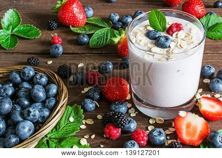 glass of yogurt with whole fresh blueberries blackberries raspberries and oatmeal on old rustic wooden table with wicker bowl and many ripe berries. Closeup Detail.