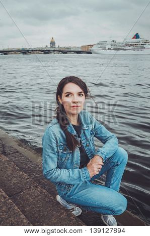 Outdoor summer lifestyle portrait of young stylish hipster woman walking near the Neva river in Saint Petersburg, Russia. Smiling female in casual clothes with hairstyle. Travel concept lifestyle. Europe summer destination.