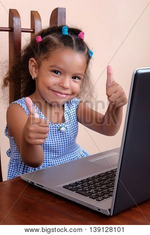Multiracial small girl using a laptop computer and doing the thumbs up sign