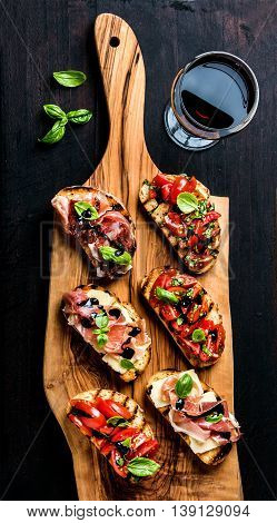 Brushetta set for wine. Variety of small sandwiches with prosciutto, tomatoes, parmesan cheese, fresh basil and balsamic creme served with glass of red wine on rustic wooden board over dark background, top view
